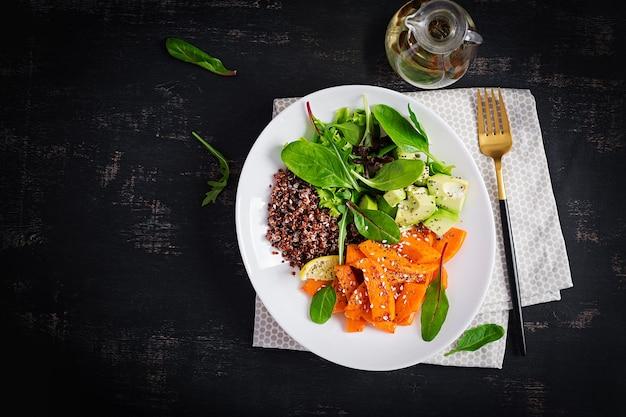 Buddha bowl met quinoa, gefrituurde schijfjes pompoen, avocado en groene kruiden