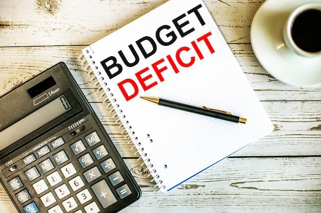 Budgetteficit geschreven op wit papier in de buurt van koffie en rekenmachine op een lichte houten tafel