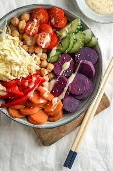 Budha kom met paarse batata, paprika, kool, zoete aardappelen, kikkererwten, komkommers op het witte linnen tafelkleed