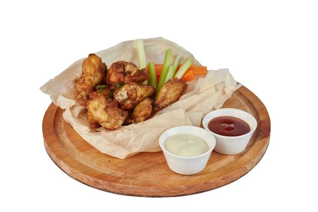 Buffalo kippenvleugels op plaat met saus, wortelen en selderij