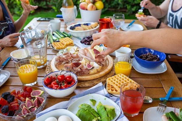 Buffet de familie zit aan het ontbijt op het terras een grote familie eet aan tafel