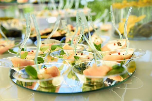 Buffettafel met een weergave van voorgerechten van zalm, zeevruchten op ronde spiegels