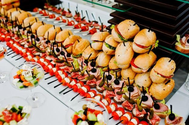Buffettafel van ontvangst met hamburgers, koude snacks, vlees en salades
