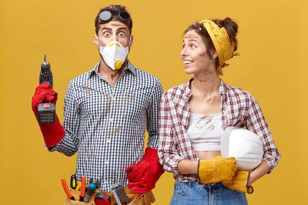 Bug-eyed man draagt beschermend masker en handschoenen met gereedschapsriem om de taille met boor bang voor moeilijkheden en veel werk staande in de buurt van zijn collega die naar hem kijkt met een glimlach