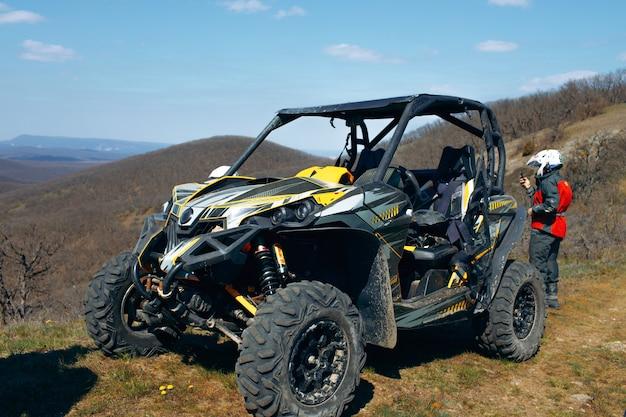 Buggy geparkeerd in bergen en bestuurder in sportuitrusting die erachter staat