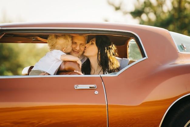 Buick rivierin retro stijl. unieke auto. moeder en zoon kussen zijn vader in het retro autoraam.