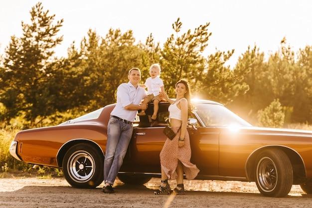 Buick rivierin retro stijl. unieke auto. schattige blonde jongen zittend op het dak van de auto. ouders omhelzen hun zonsondergang.