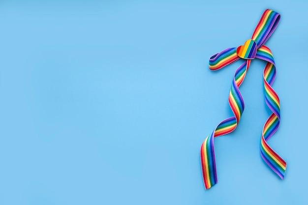 Buig van een regenbooglint met een regenbooghart op een blauwe achtergrond. lgbt-concept