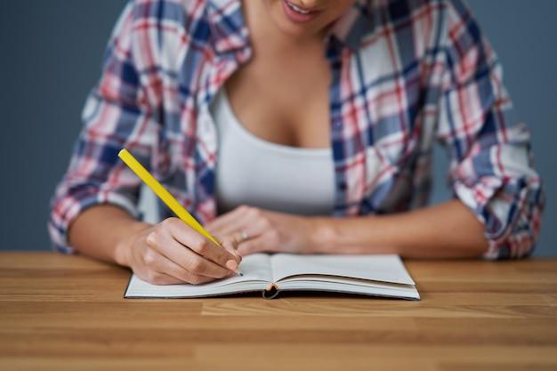 Buik die vrouwelijke student toont die thuis leert