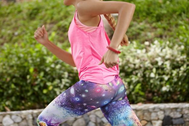 Buik van blonde vrouwelijke atleet loopt langs het pad in het stadspark, uit te werken tijdens de ochtendlooppas. jonge sportvrouw met atletisch lichaam joggen alleen in de open lucht, gekleed in stijlvolle sportkleding