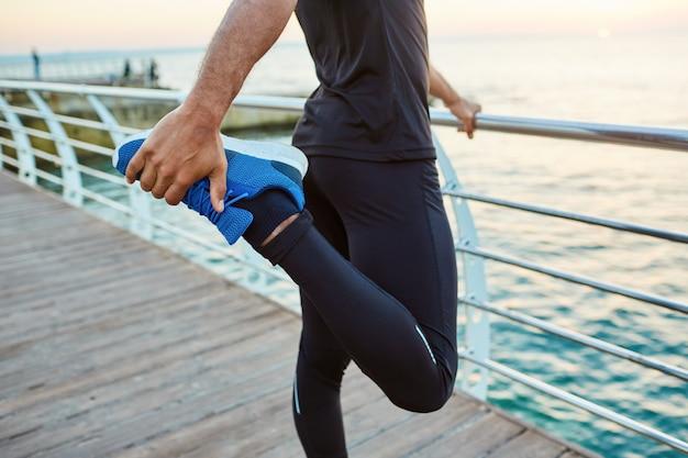 Buik van een fitte, donkere sportman die zijn spieren opwarmt, zijn benen strekt, staand quadricep voorste dijbeen strekt voordat hij 's ochtends gaat trainen, met uitzicht op zee