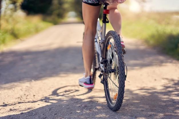 Buik van een vrouw op de fiets op het platteland