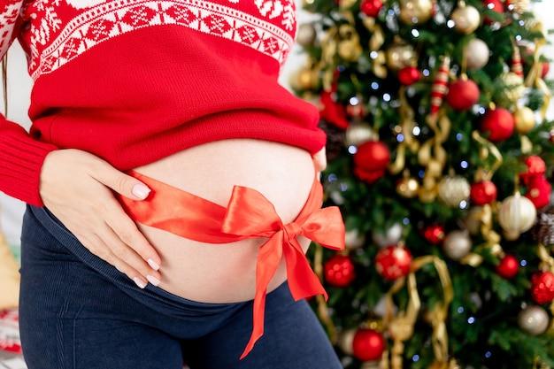Buik van een zwangere vrouw met een rode strik in een rode trui in de buurt van de kerstboom close-up, het concept van een cadeau voor nieuwjaar en kerstmis