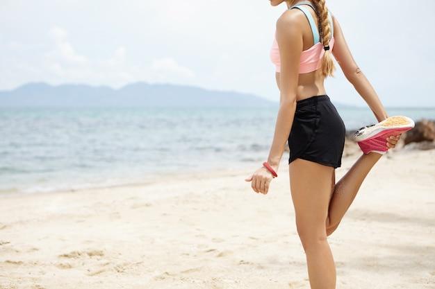 Buik van fit blonde sportvrouw met paardenstaart die haar spieren opwarmt, haar benen strekt, quadricep voor de dij strekt voordat ze 's ochtends gaat trainen, met uitzicht op de oceaan