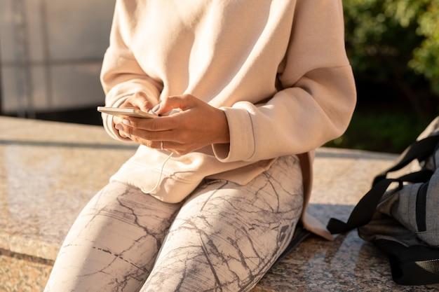 Buik van jonge hedendaagse vrouwelijke duizendjarige in hoodie en leggings zittend op marmeren tegels na buitentraining en met behulp van gadget