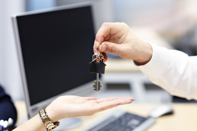 Buik van makelaar in onroerend goed en kopers handen met sleutels op kantoor the