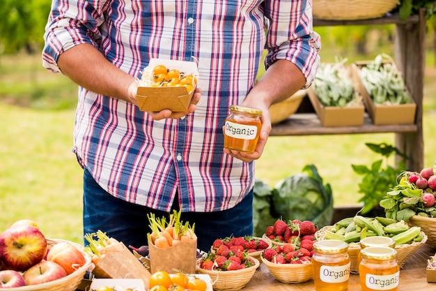 Buik van man die tomaten en domeinen verkoopt