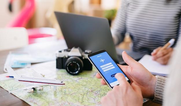 Buik van onherkenbaar stel met laptop en smartphone die vakantie plannen