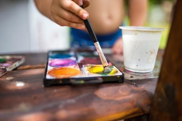 Buik van onherkenbare jongen die buiten in de zomer schildert, close-up.