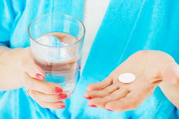 Buik van senior vrouw met medicijnen en waterglas
