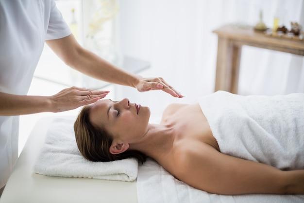 Buik van therapeut die reiki op vrouw uitvoert