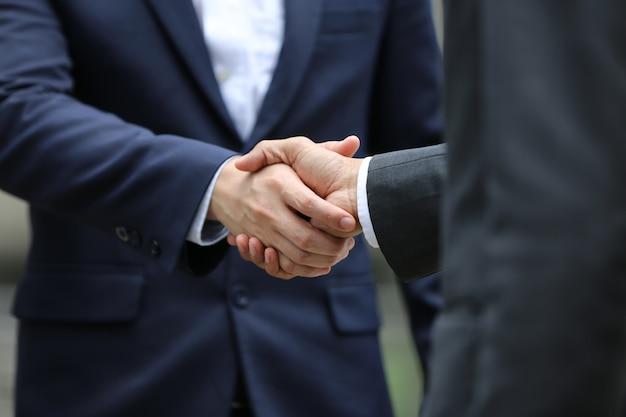 Buik van twee mensen uit het bedrijfsleven handen schudden in de buitenlucht