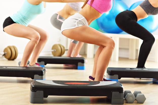 Buik van vrouwelijke groep die squats doet in de sportschool