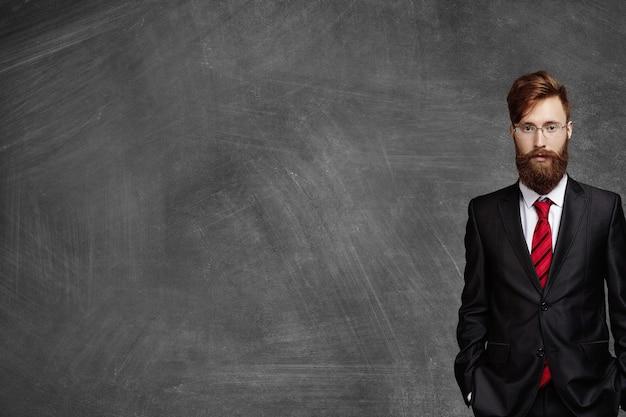 Buik van zakenman met pluizige baard, gekleed in elegant zwart pak en bril staande in kantoor tegen leeg schoolbord met kopie ruimte voor uw inhoud voordat hij zijn partners ontmoet