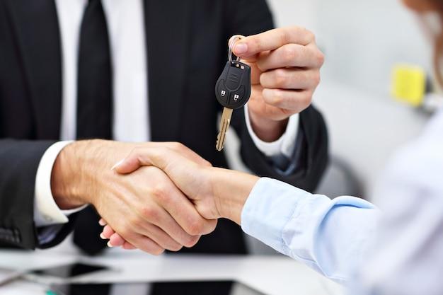 Buik van zakenmensen die handen schudden en sleutel geven
