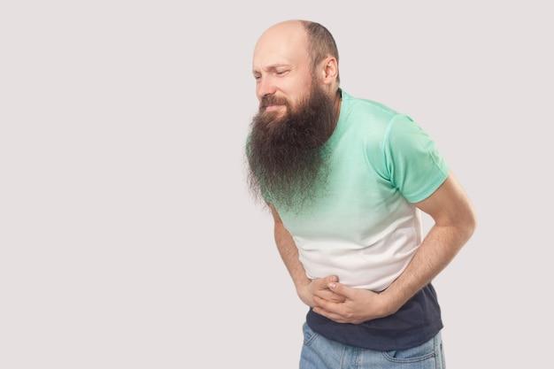 Buikpijn. portret van een zieke kale man van middelbare leeftijd met een lange baard in een lichtgroen t-shirt die staat, zijn pijnlijke buik vasthoudt en zich slecht voelt. indoor studio opname, geïsoleerd op een grijze achtergrond.