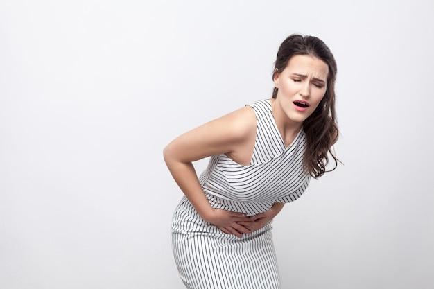 Buikpijn. portret van zieke, ongelukkige jonge brunette vrouw met make-up en gestreepte jurk die met buikpijn staat en haar pijnlijke buik vasthoudt. indoor studio opname, geïsoleerd op een grijze achtergrond.