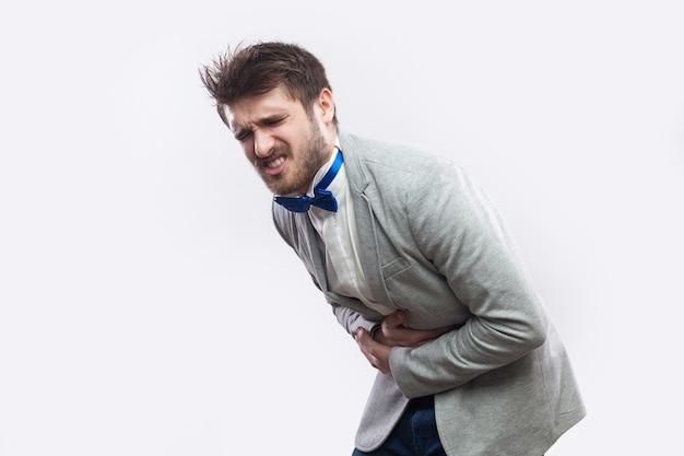 Buikpijn. profiel zijaanzicht portret van jonge, bebaarde man in casual grijs pak en blauwe vlinderdas die staat en zijn pijnlijke buik vasthoudt. indoor studio opname, geïsoleerd op lichtgrijze achtergrond.