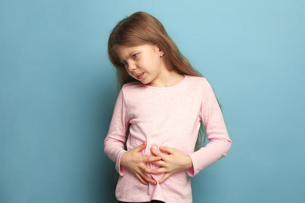 Buikpijn. verdrietig tienermeisje met buikpijn op blauw. gezichtsuitdrukkingen en mensen emoties concept
