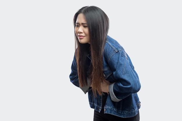 Buikpijn. zijaanzichtportret van mooie donkerbruine aziatische jonge vrouw in toevallig blauw denimjasje dat zich bevindt en pijn op haar maag voelt. indoor studio opname, geïsoleerd op lichtgrijze achtergrond.