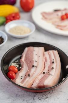 Buikspek in een pan met peperzaden tomaten en kruiden