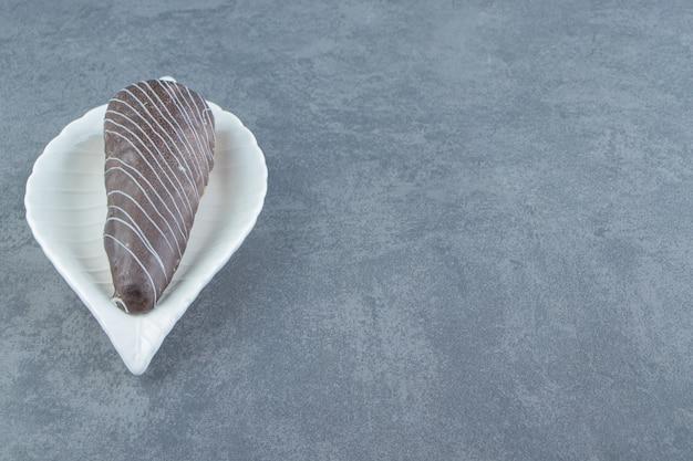 Buisvormige gebakjes geglazuurd met chocolade op witte plaat.