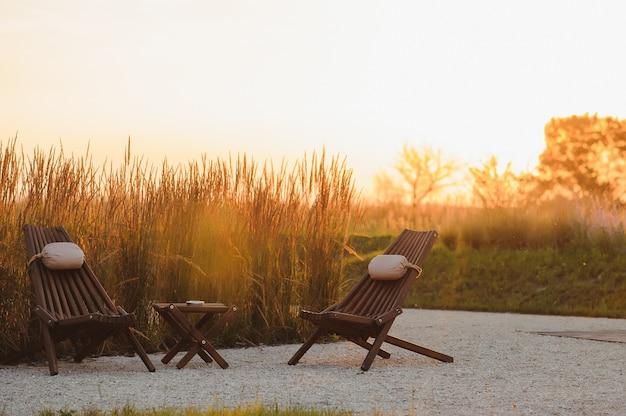 Buiten al fresco stoelen en tafel op een houten dek bij zonsondergang in het voorjaar met wijnstokken en heuvels op de achtergrond, napa valley, californië usa
