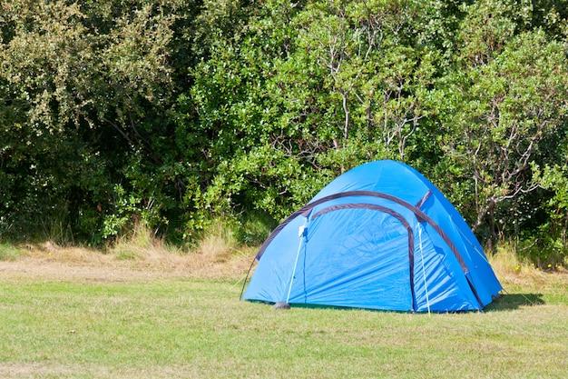 Buiten blauwe toeristische tent op een veld. horizontaal schot
