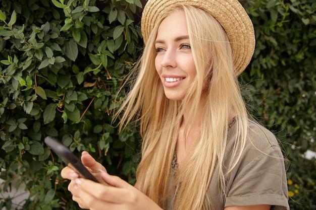 Buiten close-up met mooie jonge blonde langharige vrouw, het dragen van vrijetijdskleding en strooien hoed, telefoon in handen houden en opzij kijken met zachte glimlach