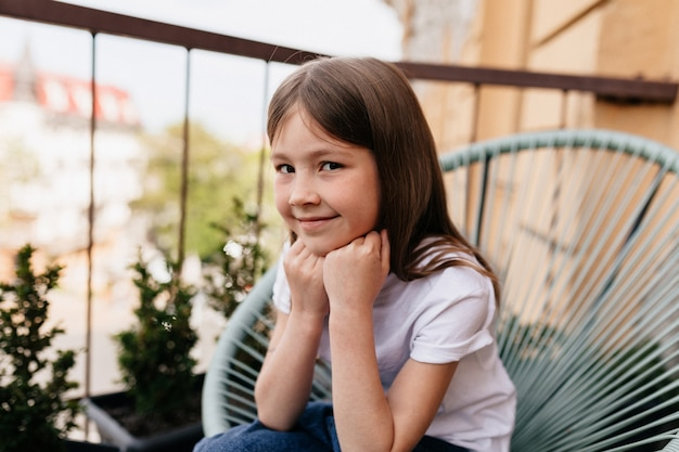 Buiten close-up portret van mooi schattig klein meisje, zittend op het balkon