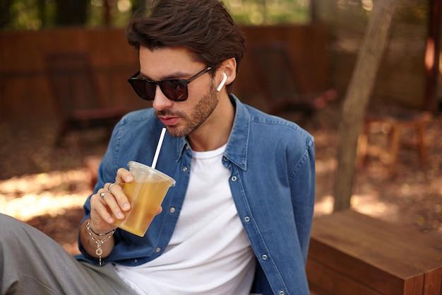 Buiten close-up van charmante donkerharige man met baard, het dragen van vrijetijdskleding en zonnebril, die zich voordeed op openbare plaats, sap met stro drinken