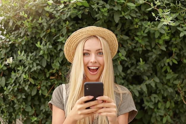 Buiten close-up van gelukkige jonge blonde vrouw in stro hoed, smartphone in handen houden en vreugdevol kijken, poseren over groene tuin op zonnige dag