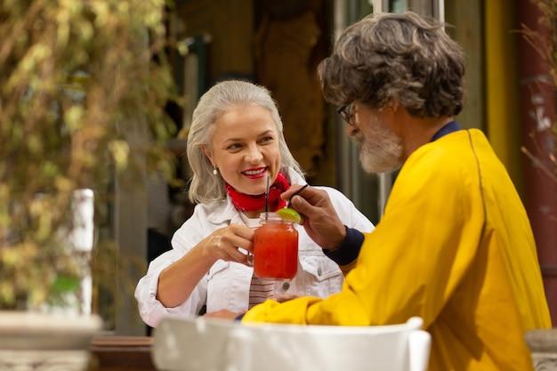Buiten datum. gelukkig getrouwd stel zit aan de tafel in het straatcafé en drinkt smoothie uit één glas.