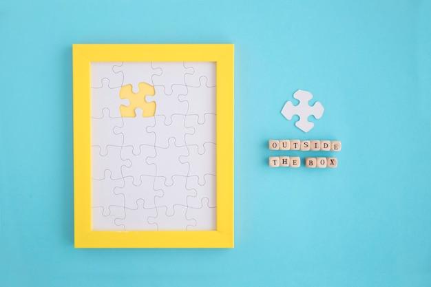 Buiten de doos blokkeert op geel kader met witte legpuzzels