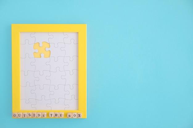 Buiten de doos puzzel gele frame met witte jig kaak stukken over de blauwe achtergrond