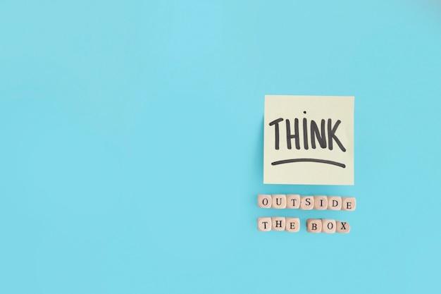Buiten de doos tekst gemaakt met houten blokken en denk tekst op zelfklevende notitie