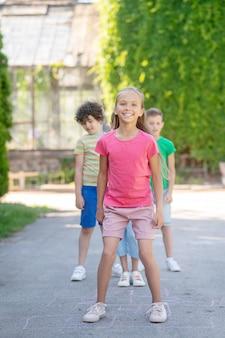 Buiten entertainment. glimlachend schattig vriendelijk meisje met vrienden in comfortabele vrijetijdskleding, de een na de ander die in het park speelt