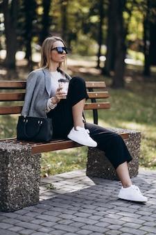 Buiten foto van blonde dame met koffie zittend op een bankje in herfstdag. mode straatstijl. een donkere vrijetijdsbroek en een romige trui en een zonnebril dragen. mode en rust concept.