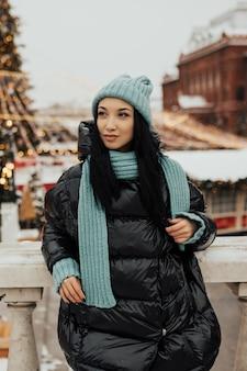 Buiten foto van jong meisje met zwart haar in gebreide blauwe muts een poseren op straat van de stad