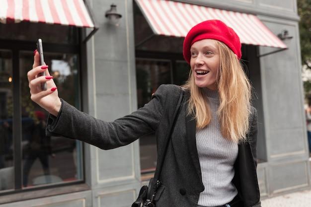 Buiten foto van jonge modieuze blonde vrouw met mooie wandeling over stad, hand opheffen met smartphone tijdens het maken van foto van zichzelf en op zoek